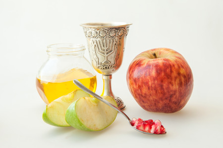 kiddush: Rosh hashana Kiddush cup honey pomegranate and sliced apple Stock Photo