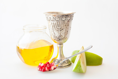 kiddush: Rosh Hashanah Kiddush cup honey pomegranate and sliced apple Stock Photo