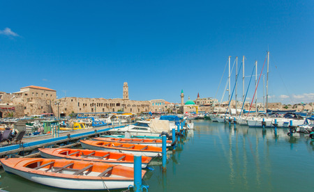 acre: Port of Acre, Israel. with boats and the old city in the background.