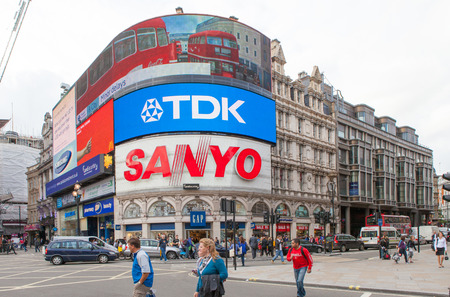 Tourists walk by Piccadilly Circus in London with its Famous neon signs advertisements of TDK and Sanyo.