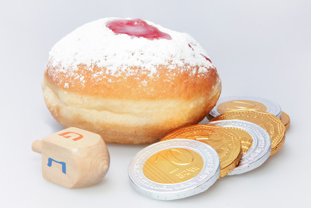 holiday food: Hanukkah doughnut and spinning top - Traditional jewish holiday food and toy. Stock Photo