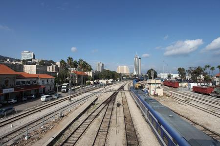 railroads: View of Haifa downtown area with railroads, train and urban landscape under blue sky. Stock Photo