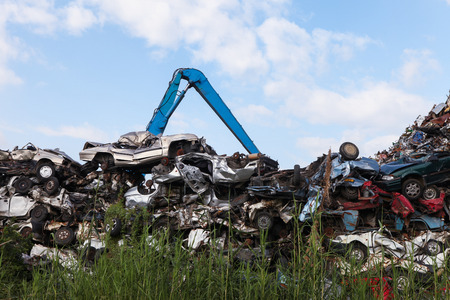 Scrap yard with crushed cars and blue sky Banco de Imagens - 34186568