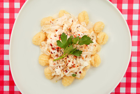Gnocchi plate on Red and white checkered table photo