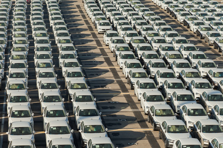 importation: Rows of new cars covered in white protective layer Stock Photo