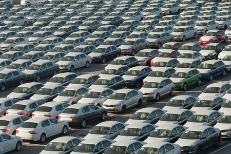 Rows of new cars covered in white protective layer Banque d'images