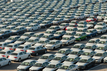 automobiles: Rows of new cars covered in white protective layer Stock Photo