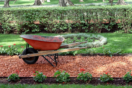 Garden work concept with wheelbarrow, soil and beautiful garden. Stok Fotoğraf