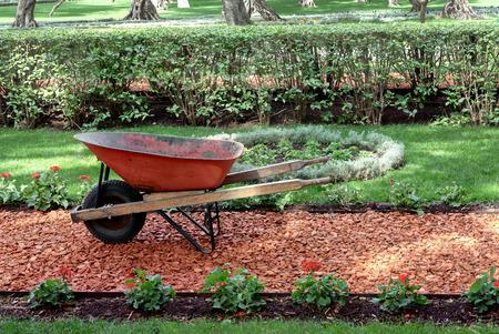 Garden work concept with wheelbarrow, soil and beautiful garden. Archivio Fotografico