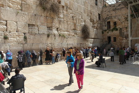 Women and tourists pray at the western wall