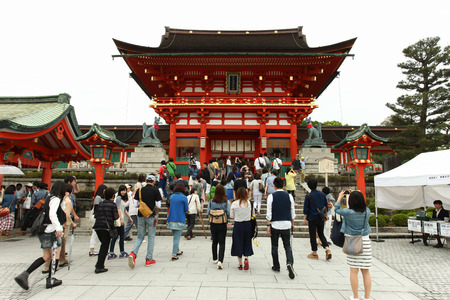 reachable: Japanese people and tourists enter Fushimi Inari Shrine in Kyoto. The road to the top of the mountain is reachable by a path lined with thousands of torii orange gates Editorial