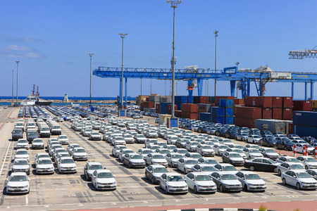 Rows of new cars covered in protective white sheet parked in Haifas port platform.