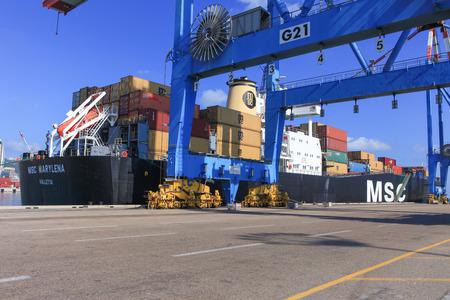 Port quai avec navire porte-conteneurs et de différentes marques et couleurs de conteneurs maritimes empilés dans une plate-forme de maintien attente pour le chargement.