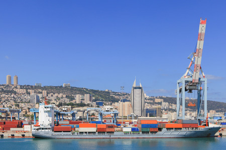 View of the city of Haifa Israel, from Haifas Port  with container ship and Carmel mountain in the background Banco de Imagens