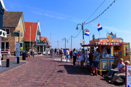 volendam: Tourists and locals at Volendams boardwalk. Volendam is a famous small town attraction thanks to its traditional costumes, port and seaside restaurants.