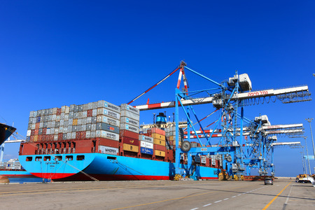 International Mega Container ship unloading containers on service trucks Editoriali