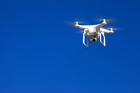 White drone hovering with blue sky in the background