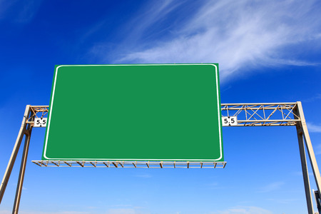 highway sign: Green highway sign with blue sky in the background