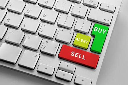 buy shares: White keyboard with finencial trading buttons