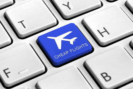 cheap: Computer keyboard with blue cheap flights button Stock Photo
