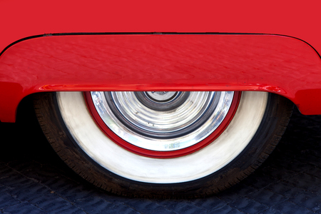 red metallic: Old car wheel covered by red metallic hood