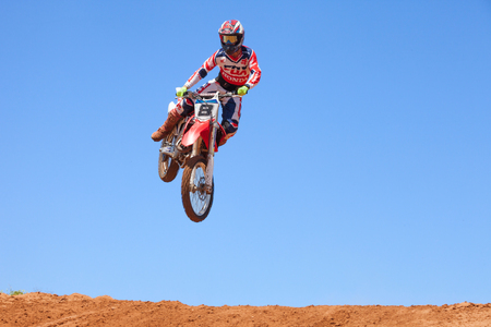 Motocross rider and bike clearing a tabletop jump during the final heat of the race Banco de Imagens - 60444923