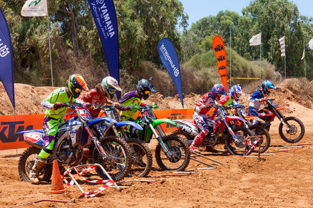 start to cross: Motocross riders and bikes clearing the starting gate at full speed during the final heat of the race