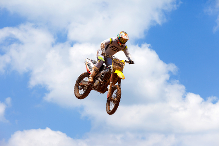 Motocross rider and bike clearing a tabletop jump during the final heat of the race. Editorial