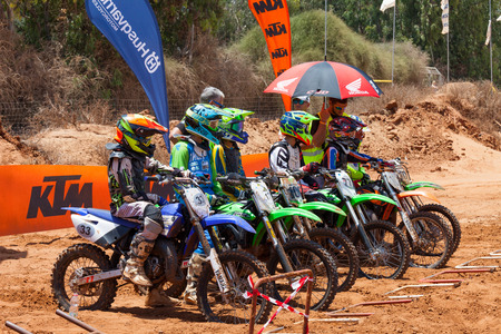 supercross: Motocross riders and bikes clearing the starting gate at full speed during the final heat of the race