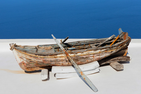 Old wooden rowing boat overlooking Santorinis bay