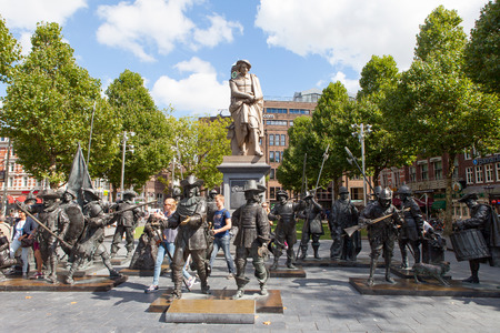 rembrandt: Sculpture of the dutch painter Rembrandt with and installation of Night watch sculptures on a sunny day in Amsterdam