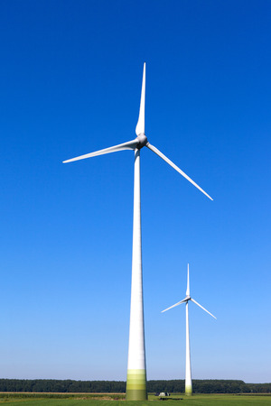 Wind turbine spinning with in a green countryside environment Stock Photo