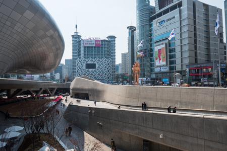 Locals and tourists walking by Dongdaemun design park (DDP), planned by Zaha Hadid with a distinctively neofuturistic design.