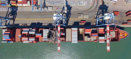 Commercial port with container ships - Top down aerial view.