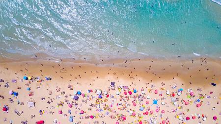 Tropisch strand met kleurrijke paraplu's - Top down luchtmening Stockfoto