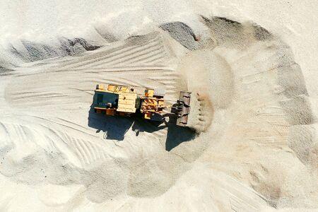 Bucket loader unloading a full scoop of Gravel onto a large storage pile.