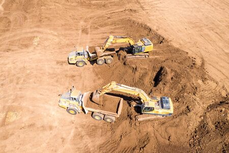 Excavator loading soil onto an Articulated hauler Truck Stock Photo