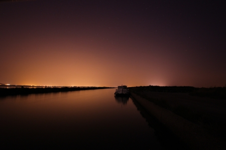 Boat moored on a river bank at night in France