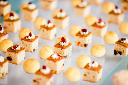 Exquisite creamy berry grape cake and coconut milk shortbread balls are arranged on the dessert table of a Western-style outdoor wedding