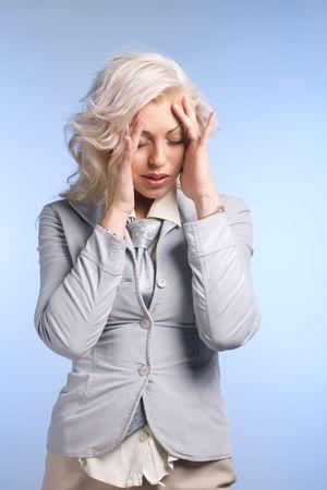 Beautyful blond woman with headache on blue background