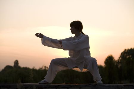 woman in white suit makes taiji chuan exercise - chinese marshal art