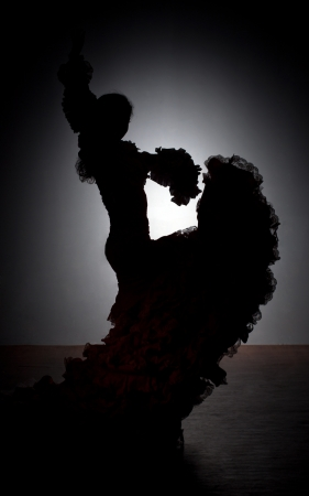 shadowgraph: Silhouette of flamenco dancer in dress on dark background