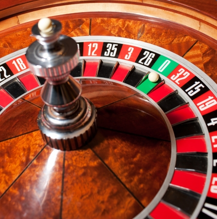 roulette wheel: Close up of roulette with ball on zero  Stock Photo