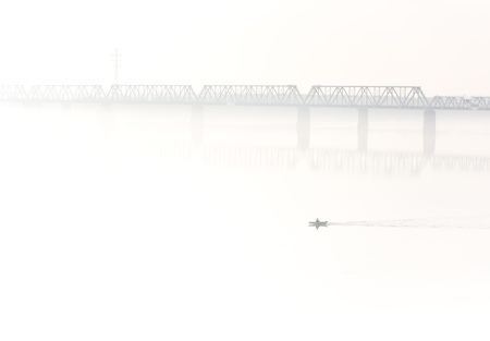 Fisherman boat across railroad bridge in fog photo
