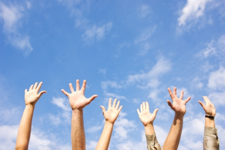Hands rised up in air across blue sky
