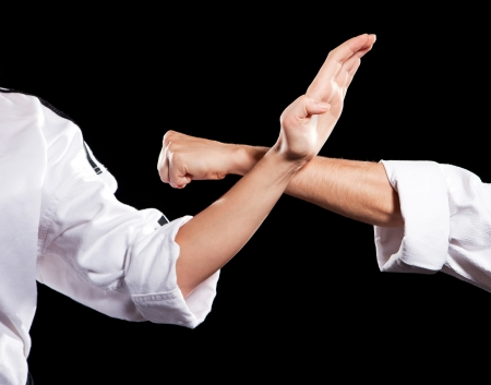 martial arts woman: Two womans fighting hands in white kimono on black background Stock Photo