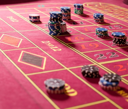 Close  up of gambling chips on red roulette table photo