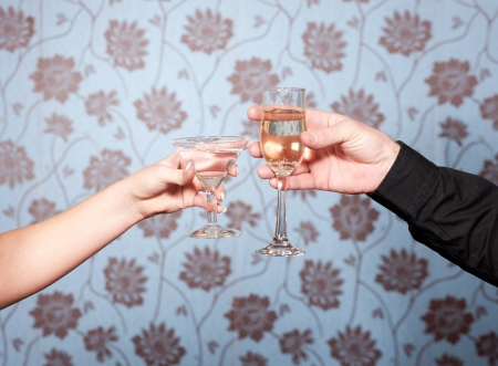Two hands with glasses of vine and Martini on blue photo