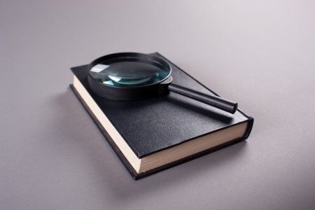 Magnifying glass on closed book on grey photo