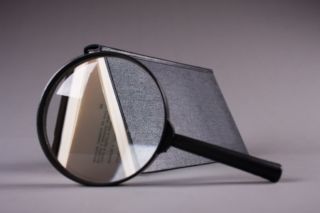book stay on grey  background across magnifying glass photo
